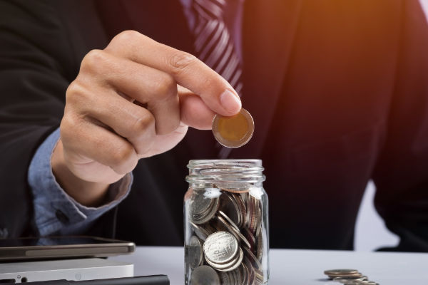 hand-putting-mix-coins-seed-clear-bottle-copyspace-business-investment-growth-concept