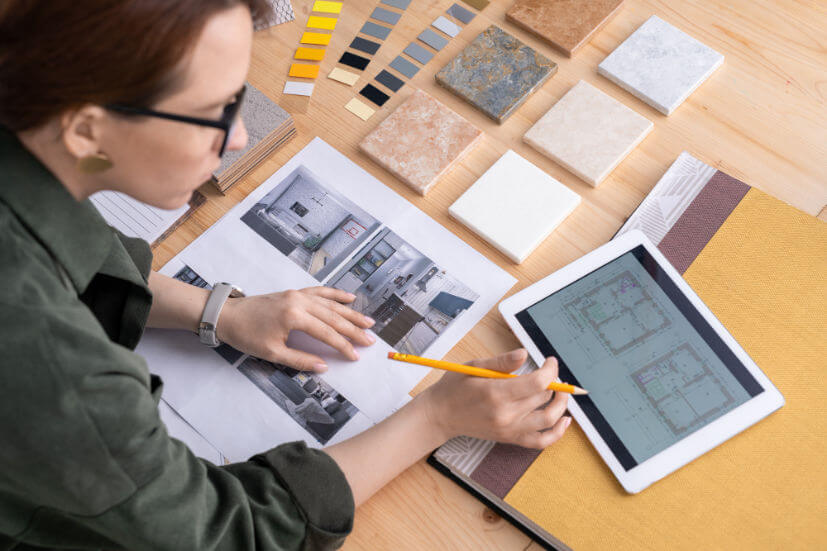 contemporary-young-female-designer-interior-bending-desk-while-looking-through-electronic-sketches-flat-touchpad