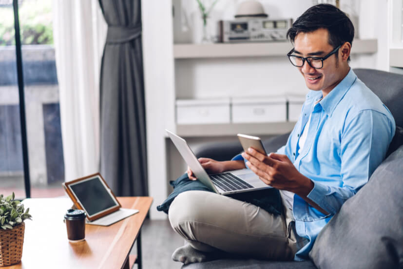 young-smiling-asian-man-relaxing-using-laptop-computer-working-video-conference-meeting-home-young-creative-man-looking-screen-typing-message-with-smartphone-work-from-home-concept